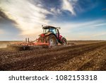 tractor cultivating field at... | Shutterstock . vector #1082153318