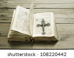 silver cross and old holy bible, wooden background - stock photo