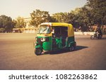 Small photo of Moto-Rickshaw, New Delhi, India. Indian taxi stands on the street against backdrop of the presidential Palace. Expensive area of the city. Tricycle vintage retro motorcycle 50-60 of the 20th century
