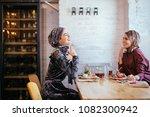 two pretty muslim women in cafe ... | Shutterstock . vector #1082300942