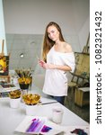 Small photo of Young amateur female artist with paintbrush in hand looking at camera in art studio