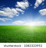 green field  blue sky and sun.  | Shutterstock . vector #1082323952