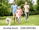 Stock photo girl and parents with golden retriever as a family in the park 1082389286