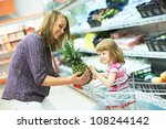 woman and little girl choosing apple during shopping at fruit vegetable supermarket - stock photo