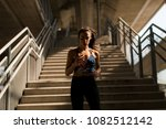young woman running alone down... | Shutterstock . vector #1082512142