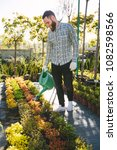 hipster gardener working in the ... | Shutterstock . vector #1082598566