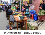 Small photo of Santiago Sacatepequez, Guatemala - November 1, 2017: Local Maya women dressed in traditional clothing make corn tortillas in the street during the giant kite festival on All Saints' Day.