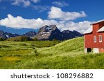 Colorful Lofoten islands in Norway during short summer north of arctic circle with typical red wooden building, dramatic mountain peaks and flowering fields - stock photo