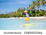 little boy surfing on tropical... | Shutterstock . vector #1083002066