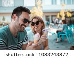 Small photo of A beautiful young couple with sunglasses are sitting outdoors and having ice-creams in cornet