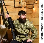 Small photo of Man with beard wears camouflage clothing in wooden interior background. Hunter, brutal hipster with gun in his hand ready for hunting. Gamekeeper concept. Macho on strict face at gamekeepers house.