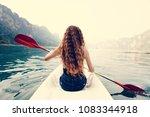 woman paddling a canoe through... | Shutterstock . vector #1083344918