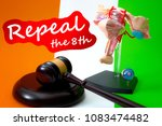 Small photo of Repeal the eighth amendment of the irish constitution, women rights legislation in ireland and feminism concept with a medical model of the female reproductive system, gavel and flag in the background