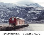 Norway, a warehouse on the pier at Narvik port on a winter day with snow, with Ankenes on the other side with mountains