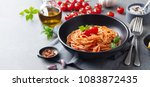 Stock photo pasta spaghetti with tomato sauce in black bowl on grey background copy space 1083872435