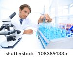 chemist looking at test tubes... | Shutterstock . vector #1083894335