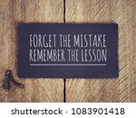 Motivational and inspirational quote - 'Forget the mistake, remember the lesson' written on a black piece of paper with background of wooden wall.