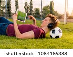 teenager laying on grass with... | Shutterstock . vector #1084186388