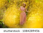 Small photo of Blondie woman, dressed in a chacked top and skirt, standing between branches of yellow blossom tree