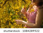 Small photo of Lady, dressed in a chacked top and skirt, standing between branches of yellow blossom tree