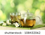 Stock photo green tea with jasmine in cup and teapot on wooden table on green background 108432062