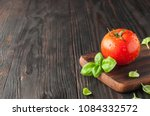 red tomato on a cutting board... | Shutterstock . vector #1084332572