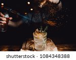 Stock photo barman prepares cocktail with orange and herbs in transparent glass on bar with alcohol uses 1084348388