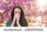 young pretty girl blowing nose... | Shutterstock . vector #1084394462