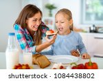 the mother is feeding her... | Shutterstock . vector #1084438802