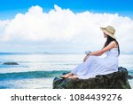 beautiful woman traveler drinking coffee and enjoying for view of the sea in the morning  on her holiday. Lady tourist in white dress sitting on the rock when the sky are blue.