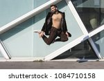 handsome indian man jumping in... | Shutterstock . vector #1084710158