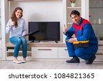 repairman repairing tv at home | Shutterstock . vector #1084821365