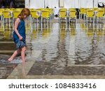 Small photo of Venice, Italy-September 7, 2014: A little girl walks through the flooded Saint Mark's Square. Every year, flooding is a continuing problem of the floating city.