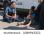 Small photo of MINNEAPOLIS - May 6, 2018: An unidentified child waits with police officers as they attempt to locate her guardian after Minneapolis's yearly May Day parade.