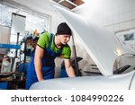 a young man in his garage finds ... | Shutterstock . vector #1084990226