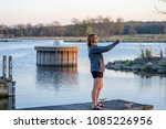 woman standing on pier taking photo of sunset with smartphone