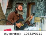 Small photo of Sozopol, Bulgaria - September 11, 2016: Street musician playing music on an acoustic guitar for the entertainment of tourists in street cafe
