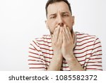 Small photo of Guy drink lots of alcohol, feeling hangover and stomach disorder. Portrait of sick funny guy in casual clothes, covering mouth with palms, feeling dizzy and wanting vomit or puke over gray wall