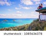 Young beautiful couple sitting on pillbox over looking Lanikai in Kailua Hawaii