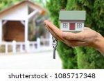 businessman holding house model ... | Shutterstock . vector #1085717348