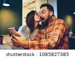 Small photo of Happy young woman kisses her bearded boyfriend who won prize in internet lottery.Amazed coung couple in love rejoices in victory in online contest on smartphone device sitting at home interior