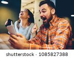 Small photo of Excited male and female hipsters rejoice in winning an internet lottery made bets on website on modern smartphone.Happy couple in love celebrating victory in online competitions enjoying success
