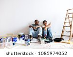 couple painting house wall | Shutterstock . vector #1085974052
