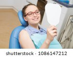 young woman checking teeth in... | Shutterstock . vector #1086147212