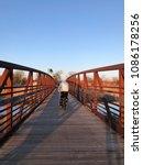 Small photo of Person biking across bridge