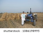 farmer standing with tractor | Shutterstock . vector #1086198995