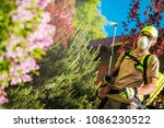 Garden Plants Insecticide. Caucasian Gardener with Professional Insecticide Spraying Equipment. - stock photo