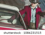 Western Wear Cowboy Driver. Caucasian Men and His Classic Vintage Car. American Transportation Theme. - stock photo