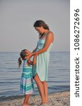 mother hugs her daughter by the ... | Shutterstock . vector #1086272696