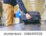 Traveler Picking Up Suitcase...